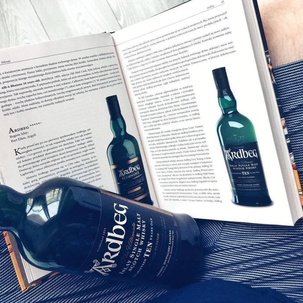 Butelka 10 letniej whisky Ardbeg na tle książki o temacie whisky